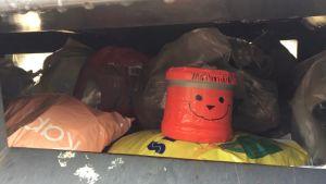 En röd plastburk med en smiley på ligger i ett plastinsamlingskärl.