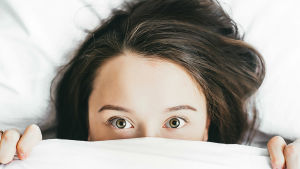 En kvinna kikar ut från täcket.