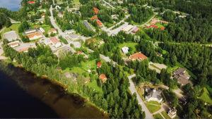 Ilmakuva Sumiaisten kylästä, näkyy kylää halkova Sumiaisraitti, sen varrella rakennusten kattoja, metsää, järvenrantaa