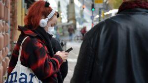 En kvinna kollar i mobilen med munskydd på, på auragatan i Åbo.