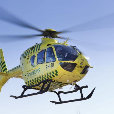En gul helikopter fotad med himmelen som bakgrund.