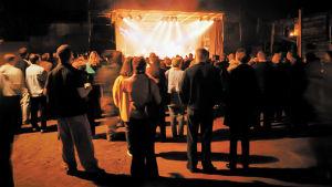 After Eightin Plutofestivaali vuonna 1998, ihmiset kuuntelevat Kemopetrol-yhtyettä sisäpihalle rakennetun lavan äärellä.