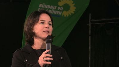 De grönas partichef talar i en mikrofon i samband med valkampanj