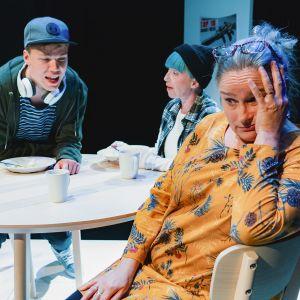 Kohtaus näytelmästä. Äiti pitelee päätään ruokapöydässä kun teini-ikäiset mellastavat