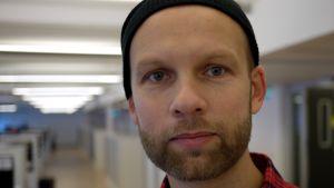 en porträttbild av robert gehring i en korridor med bakgrunden ur fokus. Han bär en rutig skjorta och en mössa.