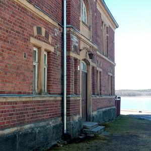 En gammal röd tegelbyggnad vid havet.