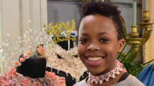 Ett porträtt av en leende flicka som har på sig ett spänt halsband, så kallad choker. Halsbandet har hon gjort själv av en rosa spets och sidenband och det är dekorerat med vita, stjärnformade pärlor.
