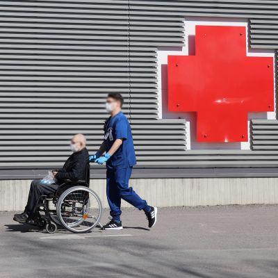 Hoitaja työntää potilasta pyörätuolissa