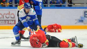 Ishockeyspelaren Damyr Ryspajev drar i skjortan på en motståndarspelare som ligger hjälplös på isen.