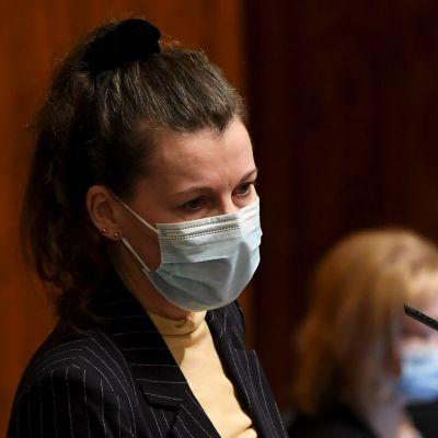 Arja Juvonen i munskydd står i riksdagen och talar.