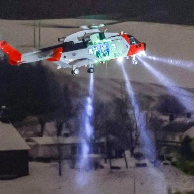 Helikopter flyger över området som där jorden rasat. Det är mörkt och räddningshelikoptern har på strålkastare.