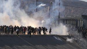 Amerikansk gränspolis använder tårgas mot migranter som försöker klättra över gränsstängslet.