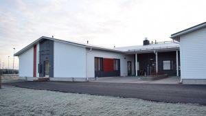 Nya almahemmet fotat utifrån, ett enplanshus i trä med vita, svarta och gråa väggar.