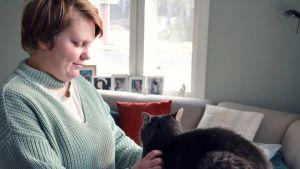 Alexandra Valkama står och klappar sin katt i ett vackert grågrönt vardagsrum.