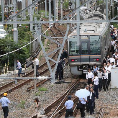 Passagerare går längs ett järnvägsspår i Osaka efter att trafiken stoppats på grund av skalvet.