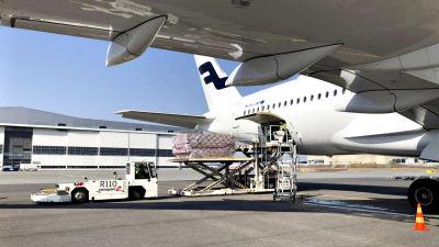 Bild på vitt Finnair-flygplan. På bilden lastas materiel ut ur planet.