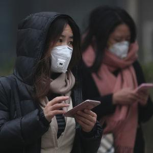 Två kinesiska kvinnor skriver på sina mobiltelefoner i utsläppsröken i Peking den 20 december 2016.