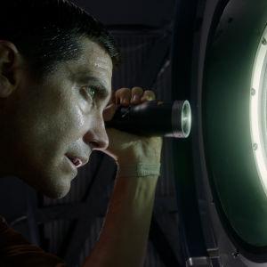 David (Jake Gyllenhaal) blinkar med ficklampa ut genom fönstret på rymdstationen.