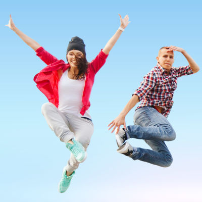 En grupp tonåringar hoppar, i bakgrunden blå himmel.