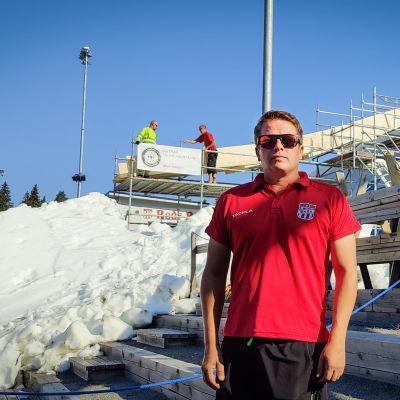 Jani Valkeapään takana on katsomorinteeseen rakennettu mäkihyppytorni ja paksu kerros lunta.