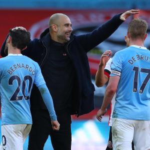 Pep Guardiola klappar två spelare på huvudet.