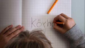 Kuvassa on lapsen kädet ja pää kumartuneena vihkon ylle. Lapsi kirjoittaa ruutuvihkoon sanaa köyhä.