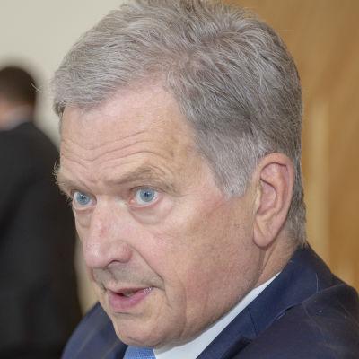 I förgrunden syns en suddig axel, i mitten av bilden sitter Sauli Niinistö.