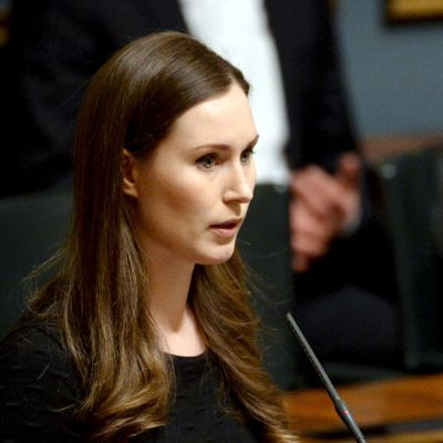 Sanna Marin i svart klänning står i riksdagens talarstol.