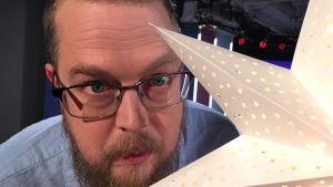 Kirjailija Tuomas Kyrö joulukuusen tähden takana Puoli seiskan studiossa