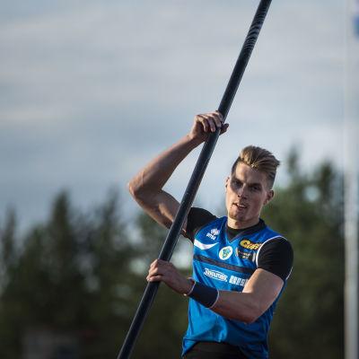 Blåklädda stavhopparen Eemeli Salomäki beredd med staven.