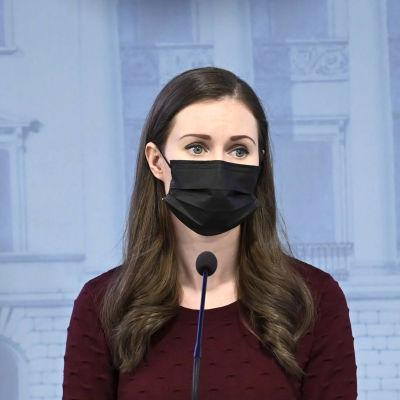 Sanna Marin i munskydd står bakom ett podium på en presskonferens.