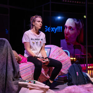 Näyttelijä Jutta Järvinen istuu sängyllä puhelin kädessä ja katselee kaukaisuuteen näytelmässä Usko, toivo, huijaus