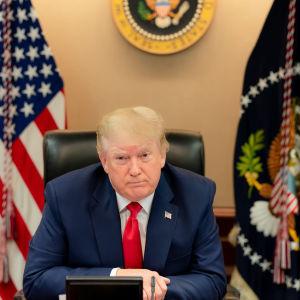 Donald Trump seuraa videoneuvottelua G20 kokouksessa. Taustalla USA:m ja USA:n presidentin liput.