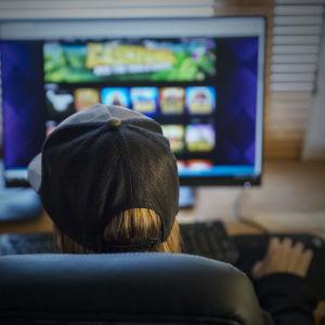 Anonyymi henkilö pelaa nettipeliä tietokoneella.