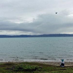 Suuri vesi etualalla, lapsi oikeassa alanurkassa rannalla istumassa,tunturimaisema taustalla.