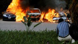 Brinnande bilar och en man som tagit skydd vid ett träd.