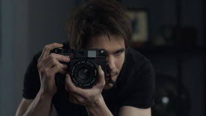 Fotografen Alex riktar kameran mot kameran.