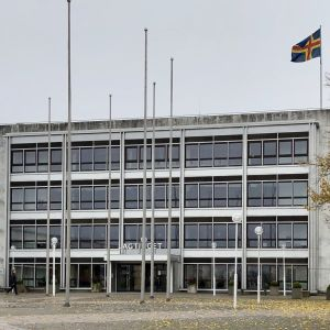 Lagtingets marmorhus i Mariehamn i höstregn, med Ålands flagga på taket