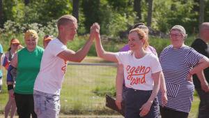Mies ja nainen löyvät kädet yhteen hymyillen kesällä urheilukentällä, taustalla hymyileviä ihmisiä.