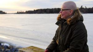 Kvinna sitter på en bänk vid en frusen fjärd. Den låga solen lyser på hennes ansikte. Hon har inget hår på huvudet.