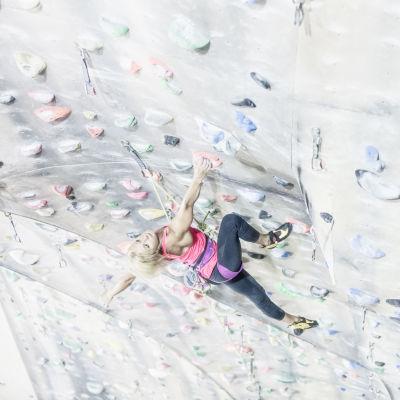 Kuvassa Maria Skyttä kiipeää kiipeilyhallin seinällä.