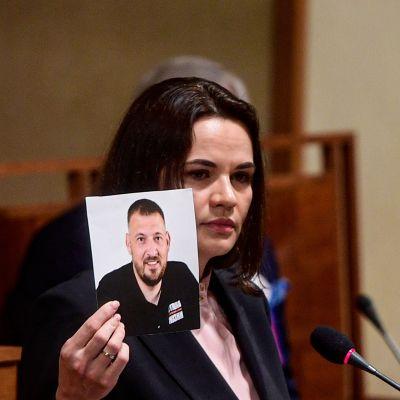 Svetlana Tichanovskaja håller upp en bild av sin man Sergej Tichanovskij då hon talar i den tjeckiska senaten9.6.2021.