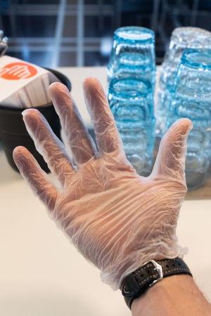 Handen har en plasthandske. Folk ombeds att använda dem när de äter på Yles lunchrestauranger.