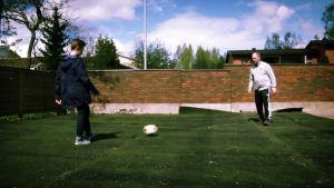 Heikki ja Eke Heinonen pelaamassa futista oman pihan kentällä.