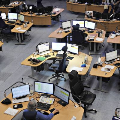 Många skrivbord i en öppen sal. Vid skrivborden sitter personal med hörlurar och mikrofoner.
