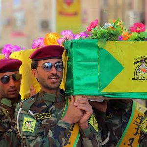 En arkivbild på milismän från Kataib Hizbollah och en kista prydd med deras flagga. Bilden är tagen under en begravning 2015 då många av milismännen dog i strider mot IS i Irak.