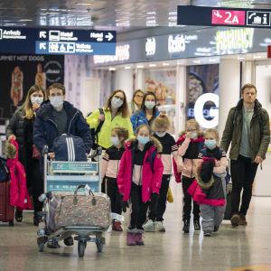 Resenärer i munskydd går på Helsingfors-Vanda flygplats.