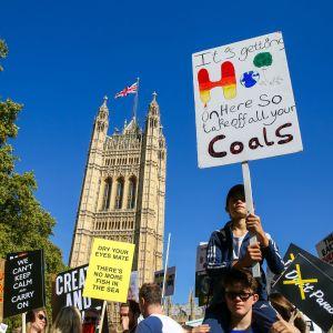 """En klimatdemonstrant i London med ett plakat med texten """"it's getting hot in here, so take off all your coals""""."""