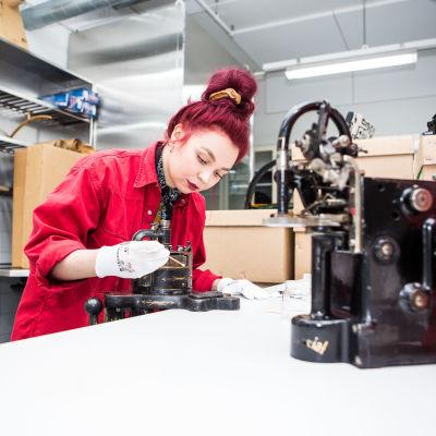 Konservointityöntekijä Milli Aho puhdistaa 1800-luvulta olevaa sukkakonetta. Paikka: Tampereen museoiden kokoelmakeskus, Rusko.
