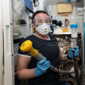 Toiletin huoltaminen ja siivoaminen on eräs avaruusaseman rutiinihommista. Tässä Serena Auñón-Chancellor on työn touhussa asiallisesti suojautuneena.